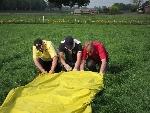Drei Männer alleine auf dem Feld. Der Ballon wird gerollt.